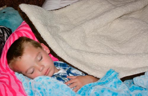 Young Boy with Cold Cuddled Up with Blankets Sleeping.